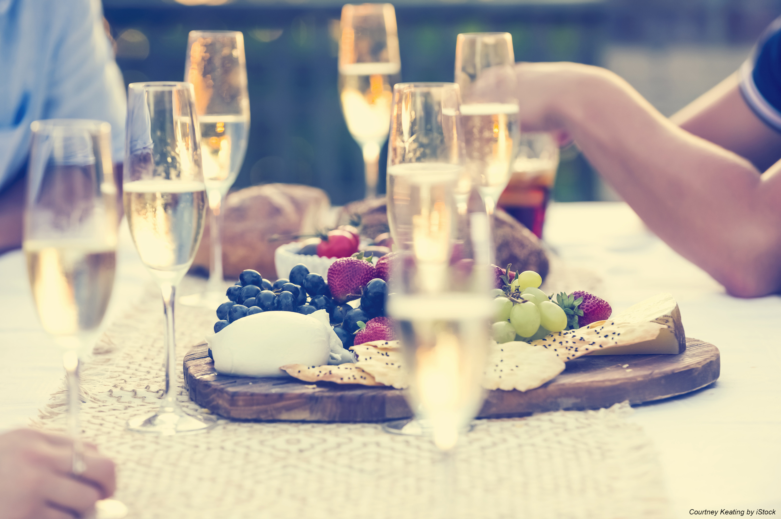 Group of friends drinking champagne. They are having a dinner party at sunset with a cheese and fruit platter. They are outdoors