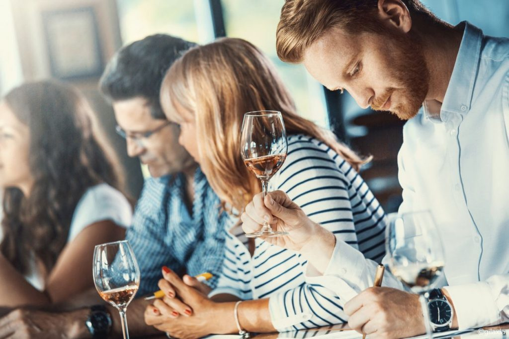 Closeup of group of people at winetasting event. They are seated side by side at a table. Mid 30's handsome man is in sharp focus, holding a glas of rose wine and writing down his impressions.