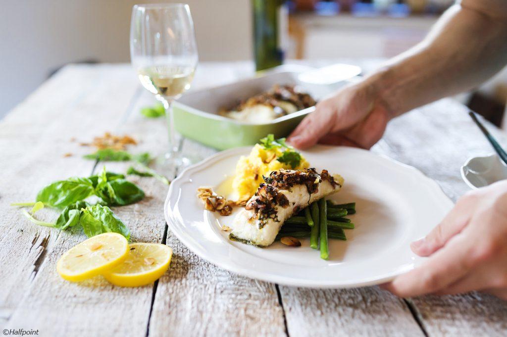 Man serving zander fish fillets on a plate